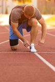 Male athlete tying laces for jogging. Man jogging on a running track. running shoes. Fitness health Stock Images