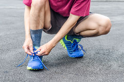 Male athlete tying laces for jogging on road Stock Photography