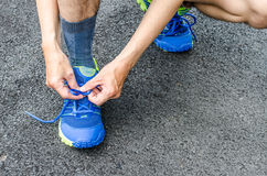 Male athlete tying laces for jogging on road Stock Image