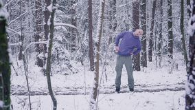Male athlete warming up in the winter forest. Inspiration and motivation concept outdoors. Man trail runner running in winter forest. Inspiration and motivation stock footage