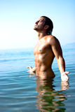 Male athlete in water. Male athlete with very muscular figure standing in sea water Stock Photos