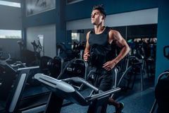 Male athlete workout on running exercise machine. Active sport training in gym Stock Images