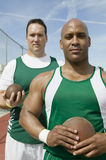 Male Athletes Holding Shot Put And Discus. Portrait of male athletes holding shot put and discus on track and field Stock Image