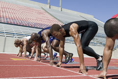 Male Athletes Lined Up At Starting Line. Group of multiracial male athletes lined up at starting line Royalty Free Stock Photos