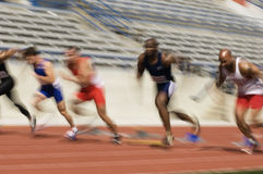 Male Athletes Racing In Stadium Royalty Free Stock Photos