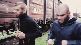 Male athletes running on railroad. Two sportsmen running on railroad along trains stock footage