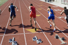 Male Athletes Running From Starting Block. Multiethnic male athletes running from starting block on track Stock Photography