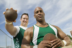 Male Athletes With Shot Put And Discus. Portrait of male athletes with shot put and discus on track and field Stock Photos