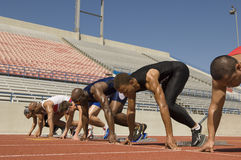 Male Athletes At Starting Blocks. Group of multiethnic male athletes at starting blocks in racetrack Stock Photos