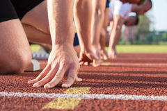 Male athletes at starting line on sunny day. Male athletes at starting line on sunny day Royalty Free Stock Photography