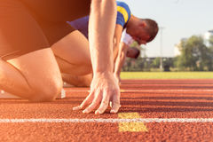 Male athletes at starting line on sunny day. Male athletes at starting line on sunny day Stock Photo