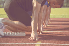 Male athletes at starting line on sunny day. Male athletes at starting line on sunny day Royalty Free Stock Photos