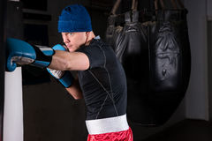 Male athletic boxer with stern look in a hat and boxing gloves t. Raining with boxing punching bag in a gym Stock Photo