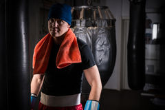Male athletic boxer with a towel around his neck in a hat and bo. Xing gloves after training with boxing punching bag in a gym Royalty Free Stock Photos