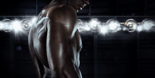Male Athletic model with muscular fit and powerful body. Sports background. Fitness instructor on black background. Male Athletic model with muscular fit and royalty free stock photos