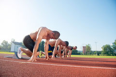 Male athletics runners on starting line without shirts. Male athletics runners on starting line without shirts Royalty Free Stock Photo