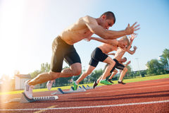 Male athletics runners on starting line without shirts. Male athletics runners on starting line without shirts Royalty Free Stock Photography