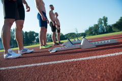 Male athletics runners on starting line without shirts. Male athletics runners on starting line without shirts Royalty Free Stock Photos