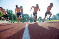 Male athletics runners on starting line without shirts. Royalty Free Stock Photo