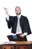 Male attorney in robe. Male bald  attorney in black robe standing with book Stock Photos