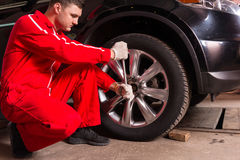 Male auto mechanic sitting near a black sedan and screwing car w. Heel by wrench in auto repair service Royalty Free Stock Images