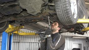Male auto mechanic with spanner working under car in garage stock video