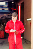 Male auto mechanic standing making notes Royalty Free Stock Images