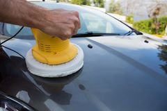 Auto service staff cleaning a car bonnet with rotating wash brush Royalty Free Stock Photo