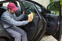 Auto service staff cleaning car door Stock Images