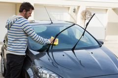 Auto service staff cleaning a car with duster Royalty Free Stock Photography