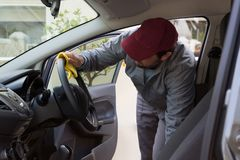 Auto service staff cleaning car interior. Male auto service staff cleaning car interior Royalty Free Stock Photos