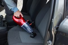 Auto service staff cleaning car with portable vacuum. Male auto service staff cleaning car with portable vacuum Stock Photo