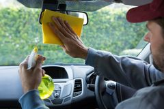Auto service staff cleaning rear view mirror. Male auto service staff cleaning rear view mirror in car Stock Photography