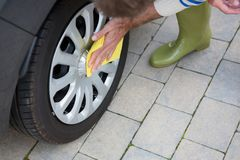 Auto service staff cleaning a tyre with duster Stock Images