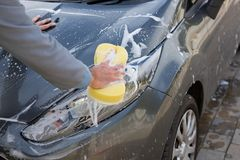Auto service staff washing a car bonnet with sponge. Male auto service staff washing a car bonnet with sponge Stock Photos