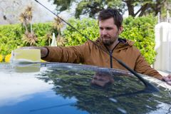 Auto service staff washing a car roof with sponge Stock Photo