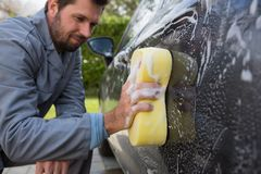 Auto service staff washing a car with sponge Stock Photos