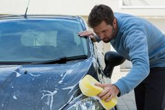 Auto service staff washing a car with sponge. Male auto service staff washing a car with sponge Royalty Free Stock Photo