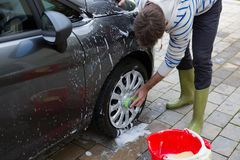 Auto service staff washing a car tyre with sponge Stock Photos