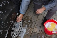 Auto service staff washing a tyre with brush. Male auto service staff washing a tyre with brush Royalty Free Stock Photo