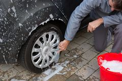 Auto service staff washing a tyre with brush. Male auto service staff washing a tyre with brush Royalty Free Stock Photos