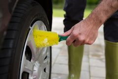 Auto service staff washing a tyre with brush. Male auto service staff washing a tyre with brush Stock Photo