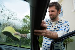 Auto service staff washing a windscreen with sponge Stock Photography