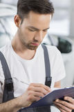 Male automobile mechanic writing on clipboard in workshop Royalty Free Stock Images