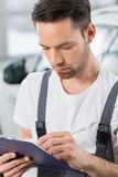 Male automobile mechanic writing on clipboard in workshop Stock Photography