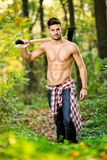 Male babe in forest. Male babe handsome lumberjack with axe in forest stock images