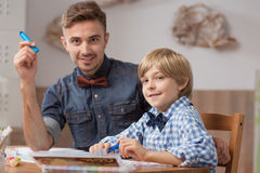 Male babysitter with boy drawing Royalty Free Stock Image