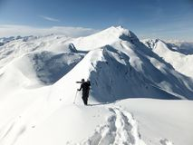 Male back country skier carrying his skis along a narrow snow ridge. A male back country skier carrying his skis along a narrow snow ridge in the Swiss Alps Stock Image