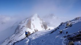 Male backcountry skier hiking to a high alpine summit in Switzerland along a rock and snow ridge in light fog. A male backcountry skier hiking to a high alpine Royalty Free Stock Photography