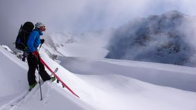 Male backcountry skier on his way up to a high alpine peak and playing around and being silly during light snowfall on an otherwis. A male backcountry skier on Stock Photo